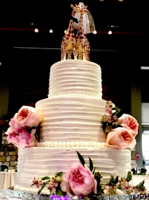 Photo of a three tier wedding cake decorated with pink roses and a couple of giraffes