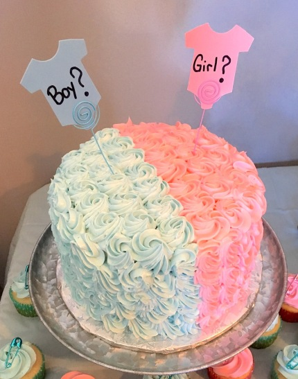 Photo of a pink and light blue cake for baby gender reveal party
