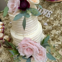 Photo of a three tier wedding cake decorated with pink and purple roses