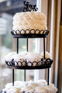 Photo of a three tier stand with a wedding cake on the top and two tiers of elegant cupcakes