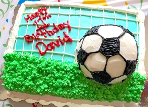 Photo of a soccer field shaped birthday cake with an edible soccer ball on the top