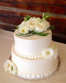 Photo of a two tier wedding cake decorated with white roses